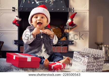 cute Little baby with red santa hat at Christmas time -  in front of a fireplace  - stock photo