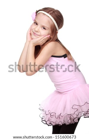 Cute little ballet dancer with beautiful hair standing in a ballet pose - stock photo
