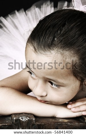 Cute little ballet girl wearing a tutu lying on an antique trunk - stock photo