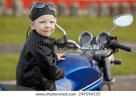 cute little biker on road with motorcycle - stock photo