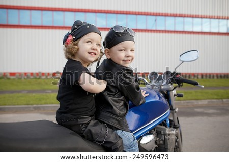 cute little bikers on road with motorcycle - stock photo