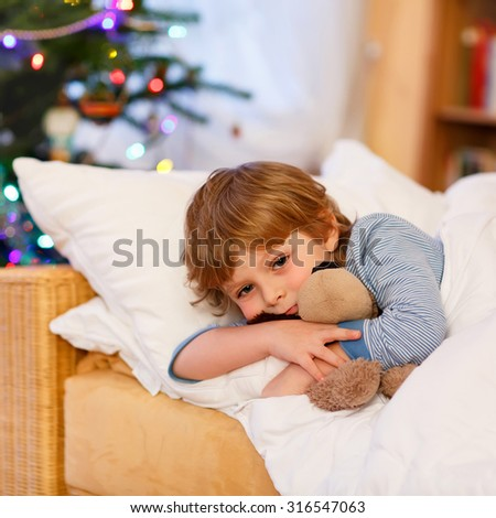 Cute little blond boy in his bed near Christmas tree with lights holding teddy bear toy. Tired child dreaming and relaxing. - stock photo