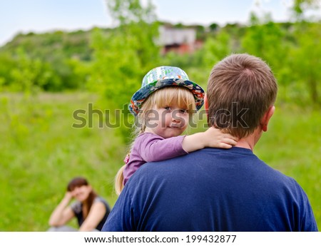 Cute little blond girl wearing a colorful hat being carried by her father looking back over his shoulder at the camera with an uncertain smile - stock photo