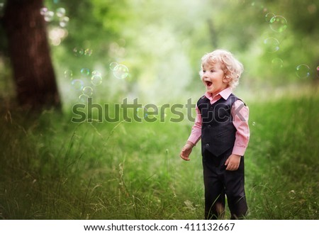 Cute little blonde boy with shiny hair standing in park and enjoying many bubbles. Happy summer day on nature. Good looking fashion kid looking on bubbles.Childhood. - stock photo