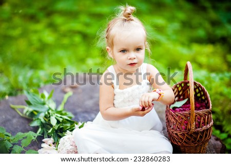 Cute little blonde girl eating raspberries from the basket - stock photo