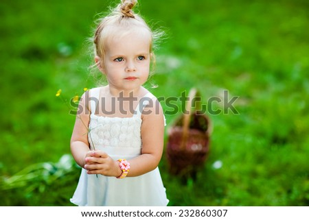 Cute little blonde girl in a white dress holding a flower in his hands - stock photo