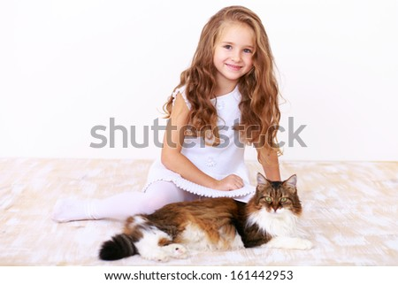 Cute little blonde girl in a white dress sitting on the floor with her fluffy cat - stock photo
