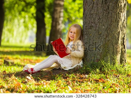 Cute little blonde girl sit near tree, read favorite book and dream - stock photo