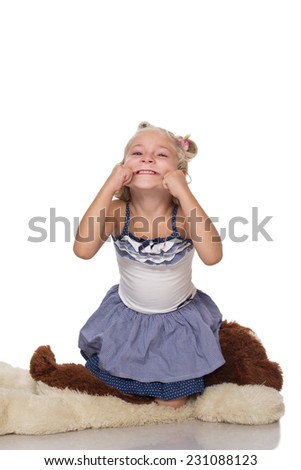 Cute little blonde girl sitting on a big soft dog toy on white background - stock photo