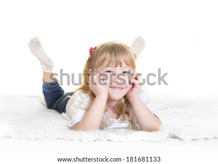 Cute little blonde girl with sweet face expression smiling and lying happy on bed at home in children lifestyle concept - stock photo
