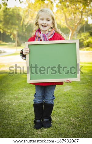 Cute Little Blonde Wearing Winter Coat and Scarf Holding a Green Chalkboard Outdoors.  - stock photo