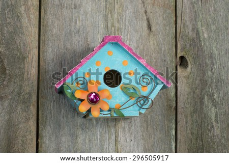 Cute little blue, yellow and pink birdhouse with orange flower and vines hanging on a rustic old wooden fence - stock photo
