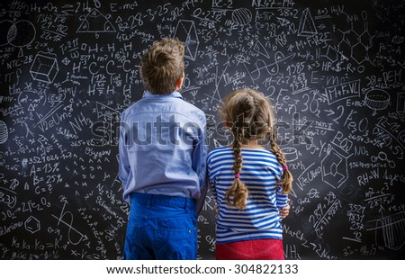 Cute little boy and girl in front of a big blackboard. Studio shot on black background. - stock photo