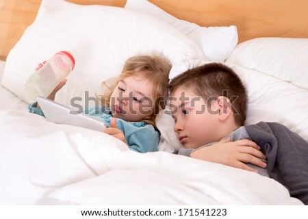 Cute little boy and girl reading a bedtime story on a tablet-pc before sleeping, lying in a big comfortable bed together - stock photo