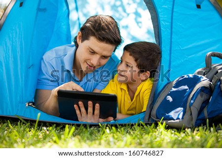 Cute little boy and his dad using a tablet computer and relaxing on a tent on a camping trip - stock photo
