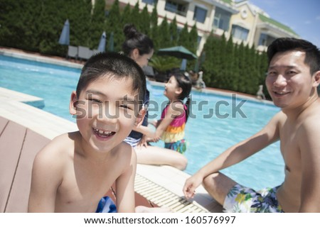 Cute little boy and his family playing in pool - stock photo