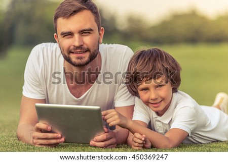 Cute little boy and his handsome young dad are holding a tablet, looking at camera and smiling while sitting on the grass in the park - stock photo