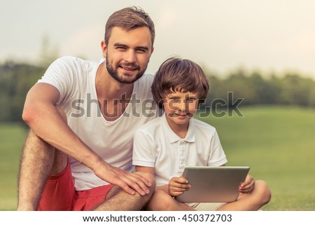 Cute little boy and his handsome young dad are looking at camera and smiling while sitting on the grass in the park. Son is holding a tablet - stock photo