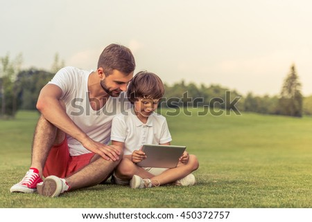 Cute little boy and his handsome young dad are using a tablet and smiling while sitting on the grass in the park - stock photo