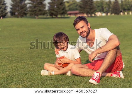 Cute little boy and his handsome young dad in casual clothes are holding a ball, looking at camera and smiling while sitting on the grass in the park - stock photo