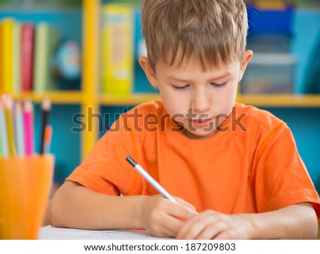 Cute little boy at lesson at junior school - stock photo