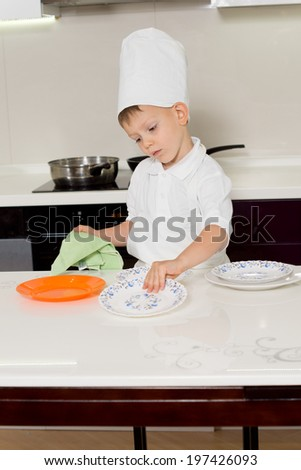 Cute little boy chef getting ready for dinner wiping and cleaning the plates before placing them on the kitchen table - stock photo