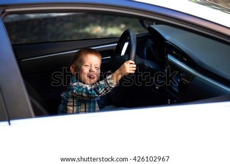 Cute little boy driving fathers car  - stock photo