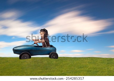cute little boy driving vintage old toy car and having fun - stock photo