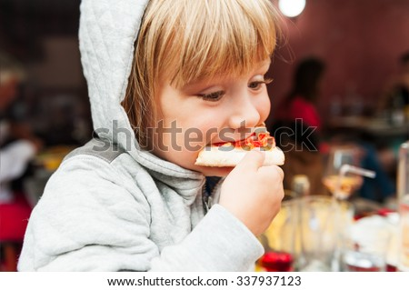 Cute little boy eating pizza in the restaurant - stock photo