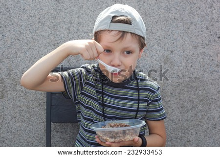 cute little boy eating porridge outdoors in summer kitchen  - stock photo