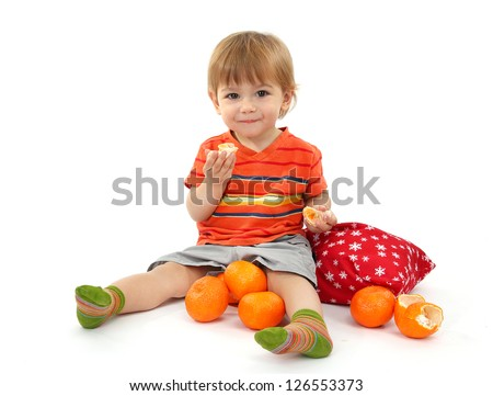 cute little boy eating tangerines, isolated on white - stock photo