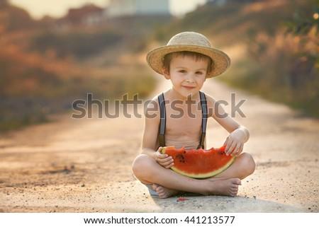 Cute little boy, eating watermelon on a rural village path, summertime - stock photo