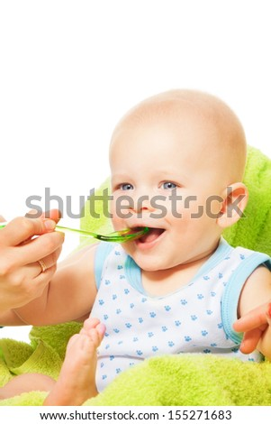 Cute little boy eats from the spoon with mothers help - stock photo