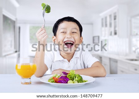 Cute little boy eats vegetable salad using fork, shot in the kitchen - stock photo