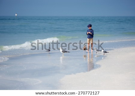 Cute little boy feeding seagulls on tropical beach, Florida summer holiday vacation - stock photo