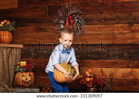 Cute Little Boy having fun in Halloween decorations. Halloween party with child holding painted pumpkin - stock photo