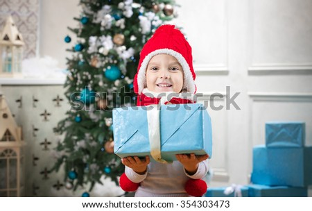 Cute little boy holding a gift against Christmas tree in background - stock photo
