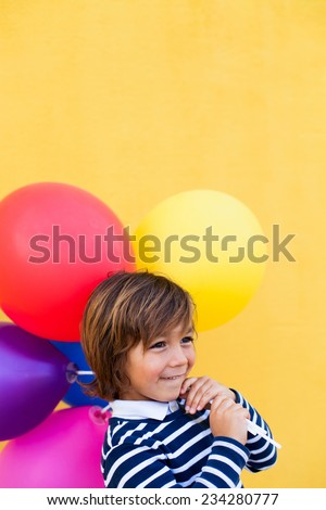 cute little boy holding colors balloons wearing a striped sweater on a yellow wall - stock photo