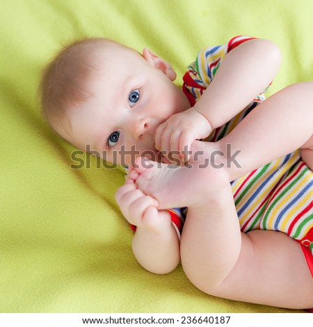 Cute little boy holding his feet in arms - stock photo