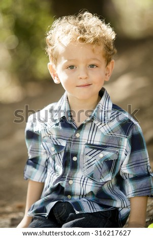 Cute little boy in a blue shirt at a park - stock photo