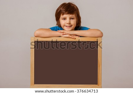 Cute little boy in a blue t-shirt leaning on a blackboard, looking in camera and smiling while standing on a gray background - stock photo