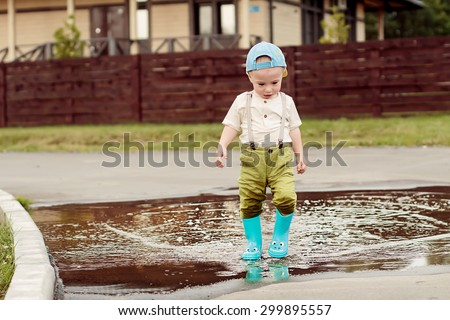 Cute little boy in cap and blue rubber boots is having fun splashing through the puddles. Image with selective focus - stock photo