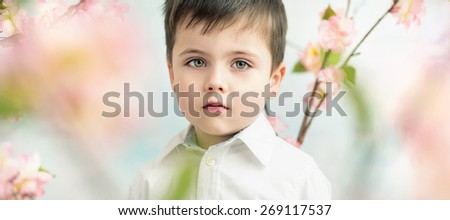 Cute little boy in flower garden - stock photo