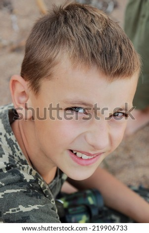Cute little boy in military uniform holding a gun in the war with enthusiasm plays in the sand - stock photo