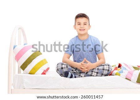 Cute little boy in pajamas sitting on a bed isolated on white background - stock photo