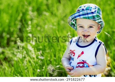 Cute little boy in panama hat playing and laughing on the green lawn - stock photo