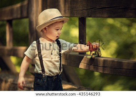 Cute little boy in straw hat playing with wooden horse on the wooden bridge. Image with selective focus and toning - stock photo