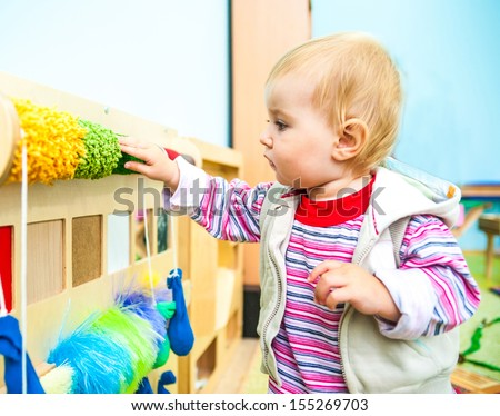 cute little boy in the classroom early development plays with  bright toys - stock photo