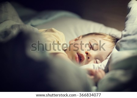 Cute little boy in yellow pyjamas is sweetly sleeping in bed with blue bed-clothes. Image with selective focus and toning - stock photo