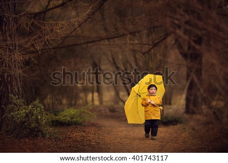 Cute little boy in yellow raincoat with yellow umbrella is walking in old park. Image with selective focus and toning - stock photo